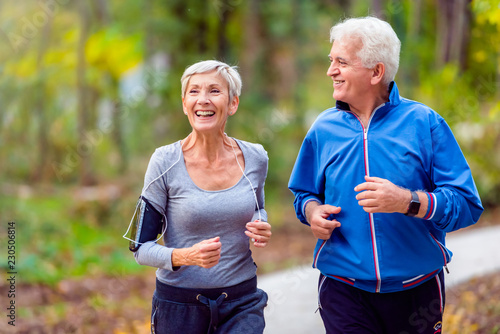 Fotomural Smiling senior active couple jogging together in the park