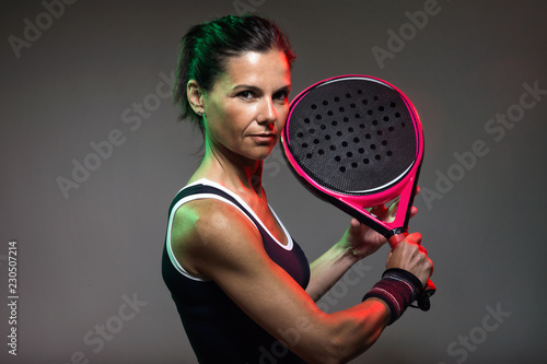 Adult fitness woman looking at camera while playing padel indoor. Isolated on black.