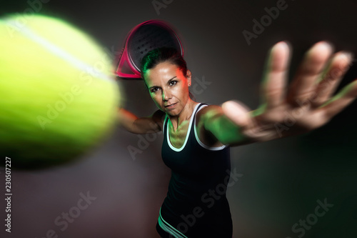 Adult fitness woman playing padel indoor. Isolated on black.