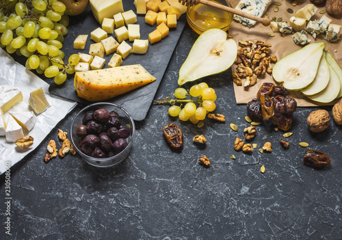 Different types of cheese on board, olive, fruits, almond and wine glasses on black stone table