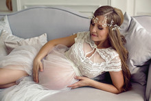 Pregnant Girl In White See-through Dress Lying On Sofa