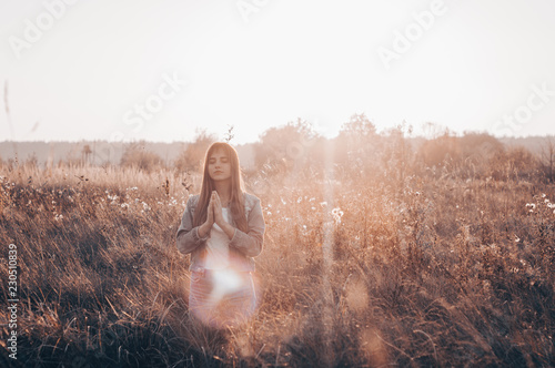 girl closed her eyes, praying outdoors, Hands folded in prayer concept for faith, spirituality and religion Fototapet