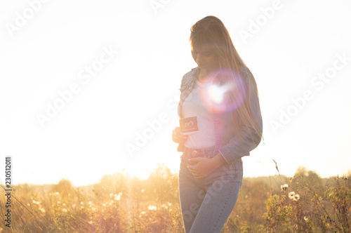 Young Pregnant Woman holding ultrasound photo at Sunset and