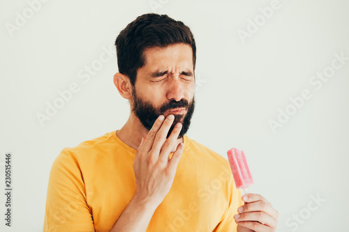 Fotografia  Man have sensitive teeth with ice on white background