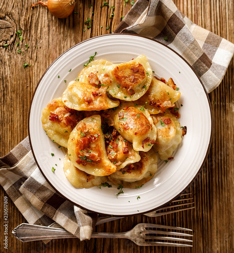 Fried dumplings stuffed with cabbage and meat sprinkled with bacon greaves and chopped parsley on a white plate on a wooden rustic table, top view.