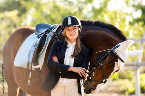 Poster de jardin Equitation Girl equestrian rider stands near the horse. Horse farm