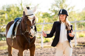 Jeździec jeździecki stoi w pobliżu konia. Stadnina koni