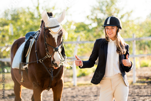 Girl equestrian rider stands near the horse. Horse farm