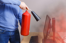 Man Using Fire Extinguisher To Stop Fire In Office. Concept Of Protection And Security