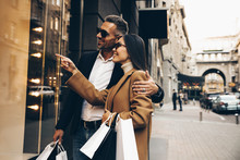 Shopping. Black Friday. Couple. Love. Man And Woman With Bags Are Looking At The Shopping Windows And Smiling While Walking Down The Street