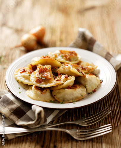 Fried dumplings stuffed with cabbage and meat sprinkled with bacon greaves and chopped parsley on a white plate on a wooden rustic table.