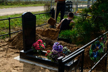 Grave-digger Digs A Grave, A Man Digs A Grave With In A Cemetery