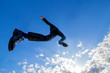 青空をバックにジャンプするスーツ姿の若いビジネスマン1人。元気・パワー・成功・挑戦イメージ