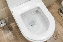White Toilet Bowl In A Bathroo...