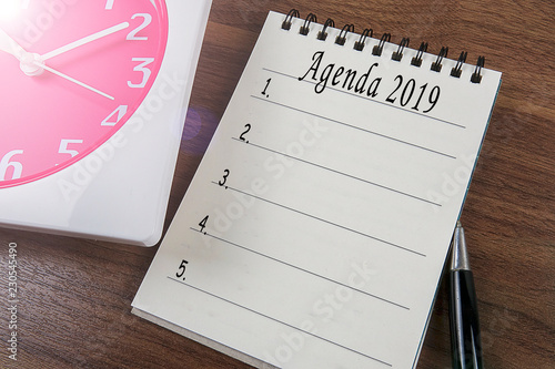 Photo  AGENDA 2019 with notepad and red clock on a wooden table.