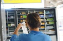 自動販売機を補充する男性
