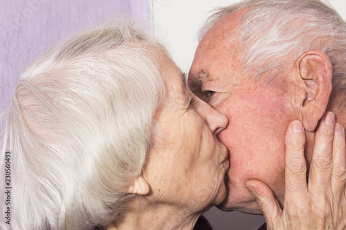 Beautiful senior woman kissing happy man at home Tableau sur Toile