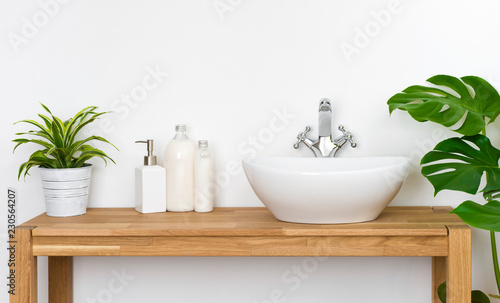 Fotografía Bathroom wooden table with washbasin, faucet, plants and soap bottles