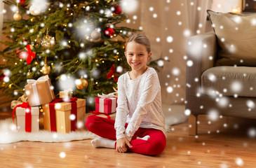 Fototapeta christmas, holidays and childhood concept - smiling girl at home