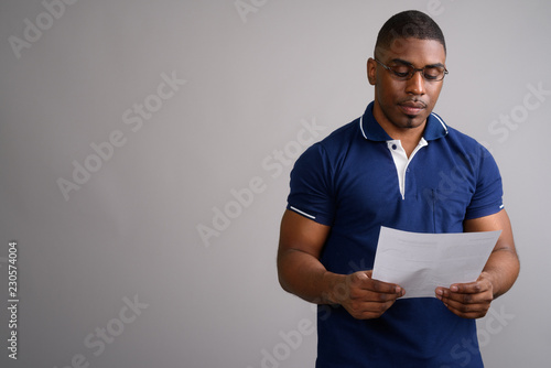 Fototapety, obrazy: Young handsome African man wearing blue polo shirt against gray