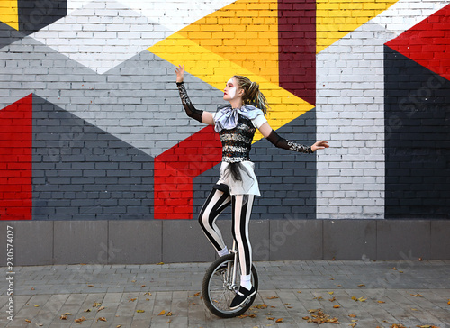 Girl clown performing with a unicycle Canvas Print
