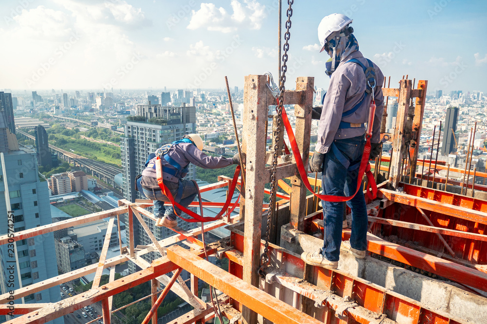 Fototapeta Construction worker wear standard personal protective equipment dismantle steel structure at height rise building project