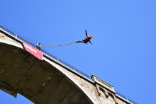 Beautiful Young Girl With Long Ponytail Performing Bungee Jump From Railway Bridge