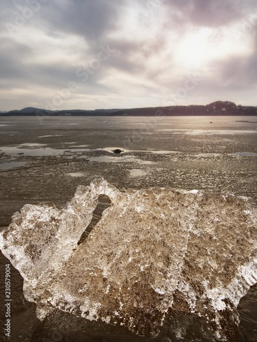 Ice fragments on empty sandy coast. Frozen sand on river coast.