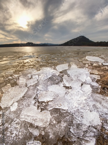 Pieces of clear natural ice on frozen lake, very close up view. Early mealting of ice