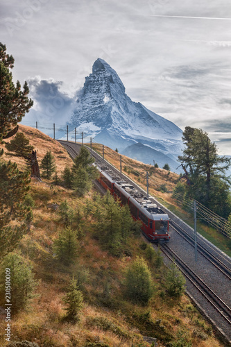Matterhorn peak with a train against sunset in Swiss Alps, Switzerland Wallpaper Mural
