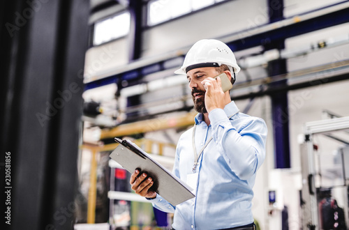 A portrait of an industrial man engineer with smartphone in a factory, working Fototapet