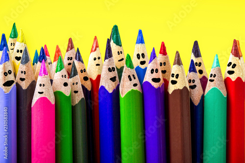 Photo  colored pencils with drawn cartoon faces, on an yellow background, a holiday con