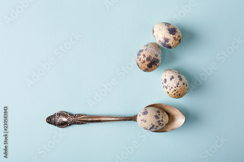 Top view of vintage teaspoon & speckled quail eggs on light blue background in minimal style. Healthy food, still life.