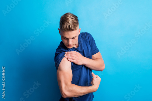 Canvas Portrait of a cheerful young man in a studio, flexing muscles.