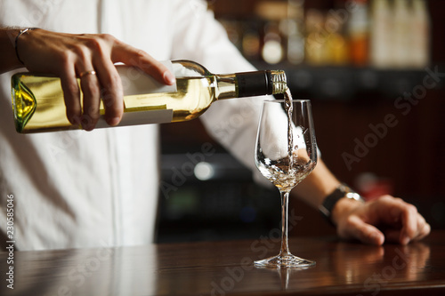 Fototapeta Male sommelier pouring white wine into long-stemmed wineglasses. obraz