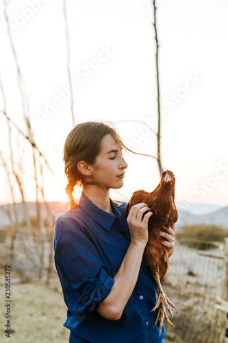 Young woman with a brown hen