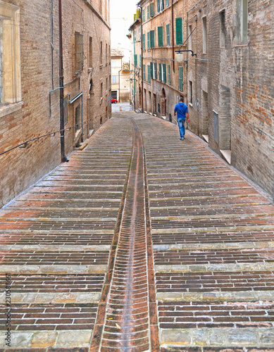 narrow street with lonely man between old historical buildings in old city of Macerata, Marche Italy