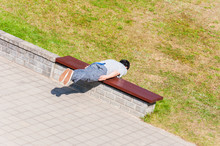 Man Lying On Bench Transversely Like Straight Plank