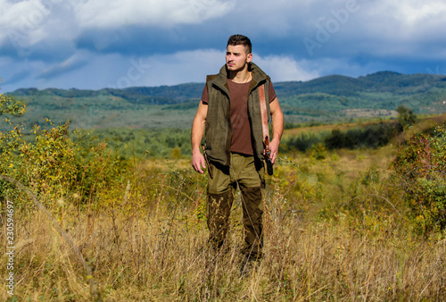 Guy bearded hunter spend leisure hunting on birds. Hunting hobby concept. Regulation of hunting. Man muscular brutal guy gamekeeper nature background. Hunter rifle gun stand top of mountain