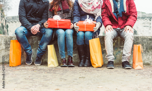 Photo Group of friends sitting outdoor with shopping bags