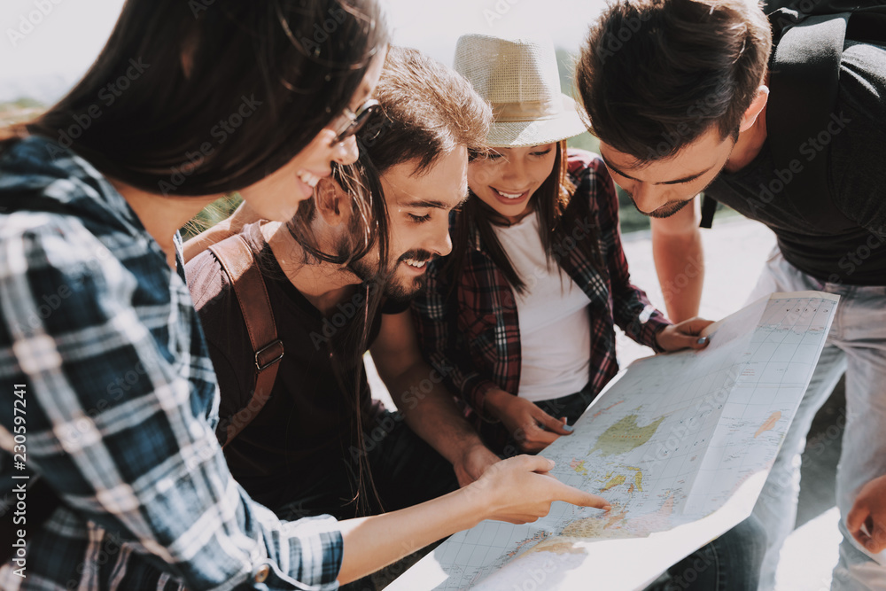 Fototapeta Group of Young Smiling People Holding Paper Map