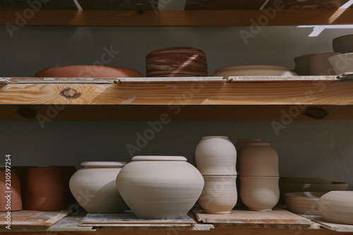 ceramic bowls and dishes on wooden shelves at pottery studio Fototapet