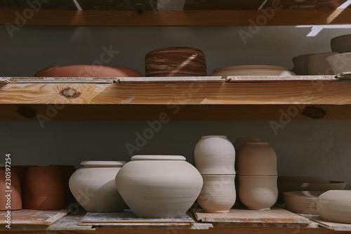 Obraz na plátně ceramic bowls and dishes on wooden shelves at pottery studio