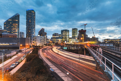 Urban view with skyscrapers, blurred train and traffic light trails Canvas Print