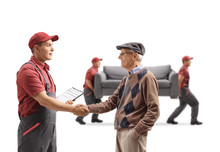 Senior Man Shaking Hands With A Mover, Movers Carrying A Couch In The Back