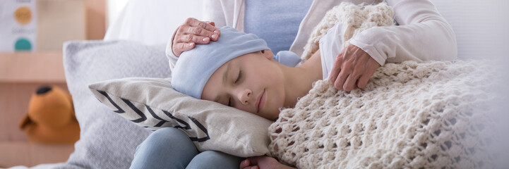 Panorama of caregiver supporting sleeping sick child with cancer in the hospice