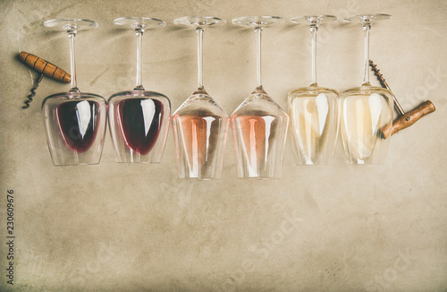 Flat-lay of red, rose and white wine in glasses in row and corkscrews over grey concrete background, top view, wide composition. Wine bar, winery, wine degustation concept