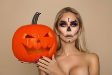 Sexy Blonde Woman In Halloween Makeup  Hold A Pumpkin On A Beigek Background In The Studio. Make-up Skeleton, Monster And Witch