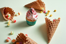 Round Frame Of Assorted Candy And Waffle Cones With Cupcake On Green Background. Dessert Concept.
