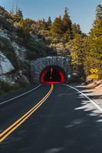 Highway Road, Yellow Double Line Leads To A Tunnel With Red Light Inside